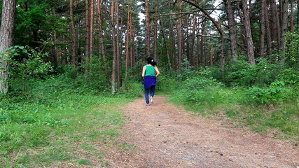 Woman running on pine forest trail