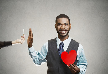 Portrait Young man says no to smoking, holding red heart