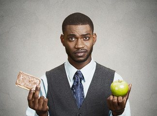 Cookie versus apple, healthy diet choices, grey wall background