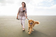 adult woman walking a golden retriever dog at the beach