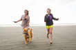 woman and child running with dog at the beach