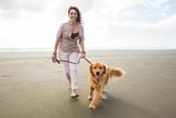 adult woman walking a golden retriever dog at the beach