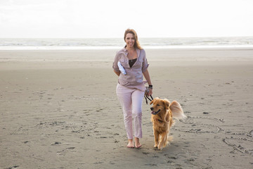 woman walking her dog at the beach