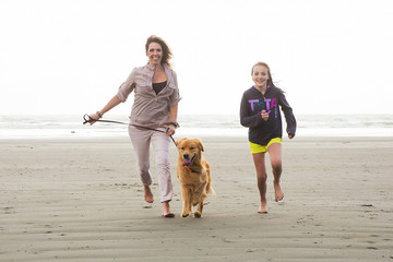 woman and child walking dog at the beach