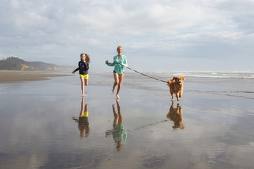 two girls running with a dog at the beach