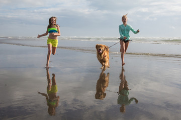 children running with a golden retriever