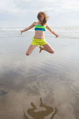 young girl jumping high at the beach