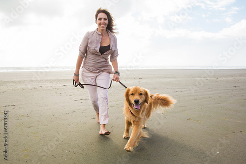 adult woman walking a golden retriever dog at the beach - 67973542