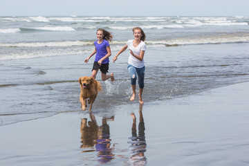 young girls running fast at the beach with a dog