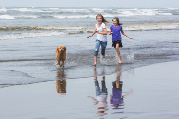 kids running at the beach with a golden retriever dog