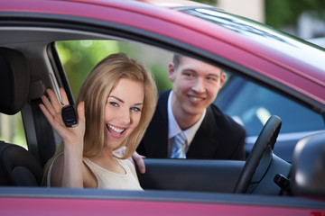 Woman Showing Key In Car With Salesman In Background
