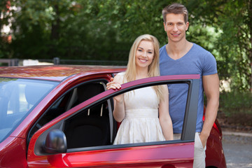 Happy Couple Standing By New Car Door