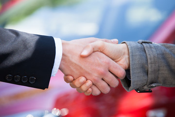 Car Dealer And Female Client Shaking Hands At Dealership