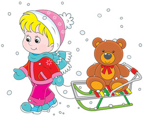 Little girl walking with her sledge and toy bear