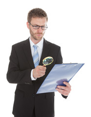 Businessman Examining Document On Clipboard