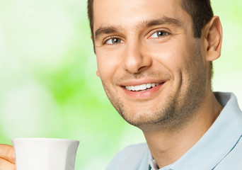 Happy smiling man drinking coffee, outdoors