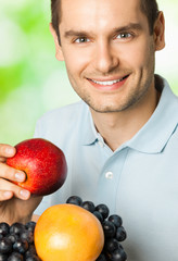 Happy smiling man with plate of fruits, outdoors