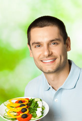 Happy smiling man with plate of salad, outdoors