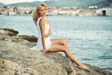 Alluring woman on the rocky beach