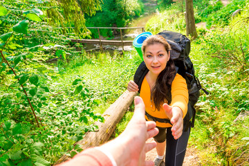a man takes a woman's hand in a hike