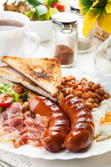 Full English breakfast with bacon, sausage, egg, beans and juice