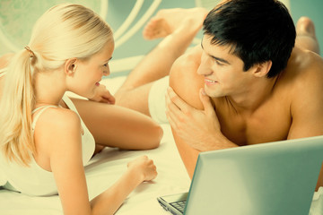 Young couple working with laptop at bedroom