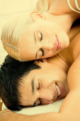 Young attractive happy amorous couple at bedroom
