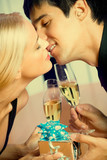 Couple with champagne and gift, kissing at party