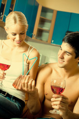 Couple celebrating with red wine, at home