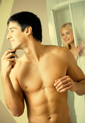 Shaving man and young woman at bathroom