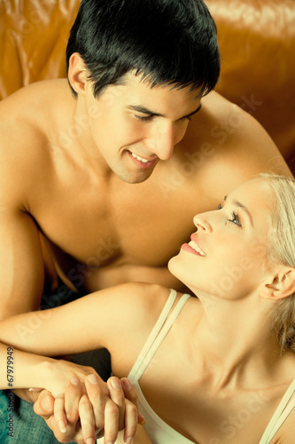 Young amorous couple embracing at home