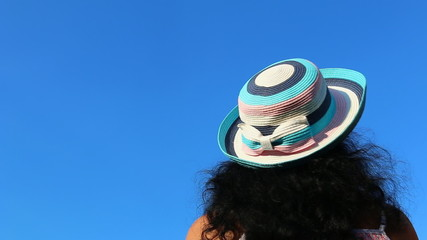 Backside of long haired woman head with hat isolated on blue