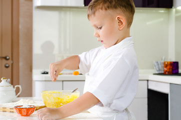 Small boy in a white apron standing baking