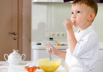 Cut little chef tasting his batter mixture
