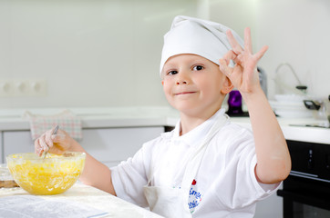 Proud little boy baking in the kitchen