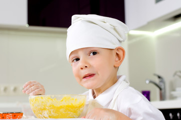 Young boy in a toque learning how to cook
