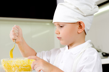 Cute little chef tasting his cooking