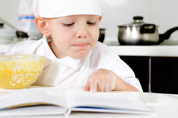 Small boy learning to cook checking his mixture