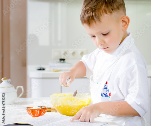 Little boy learning to bake reading the recipe