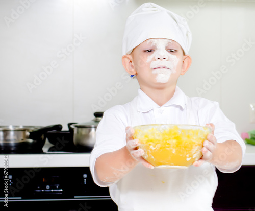 Proud little boy chef with a face full of flour