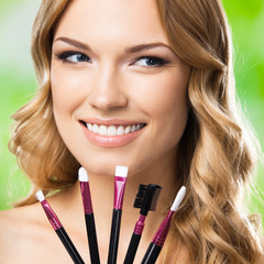 Smiling woman with make up tools, outdoor