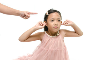 Little girl covering ears while mother scolding