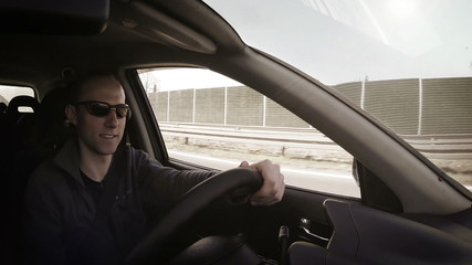 Attractive man smiling during auto trip inside car