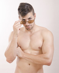 Naked man posing with sunglasses