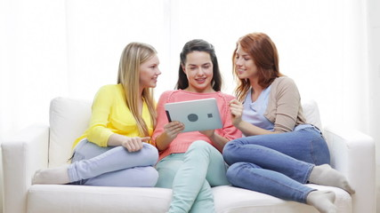 two smiling teenage girls with tablet pc at home