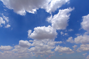 White clouds in a deep blue sky.