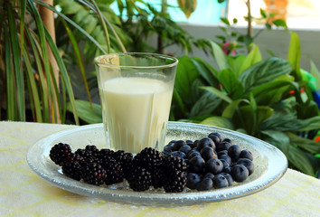 Glass of milk, blackberries and blueberries.