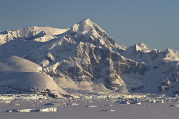 mountains and frozen ocean with icebergs of the Antarctic Penins