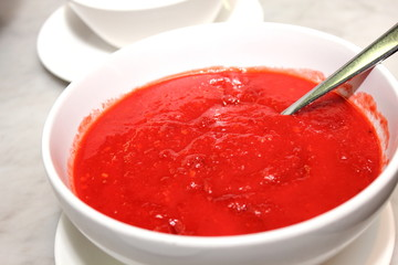 spoon in the bolw with red sauce.