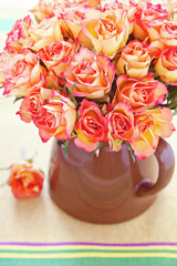 fresh orange roses in a jug .